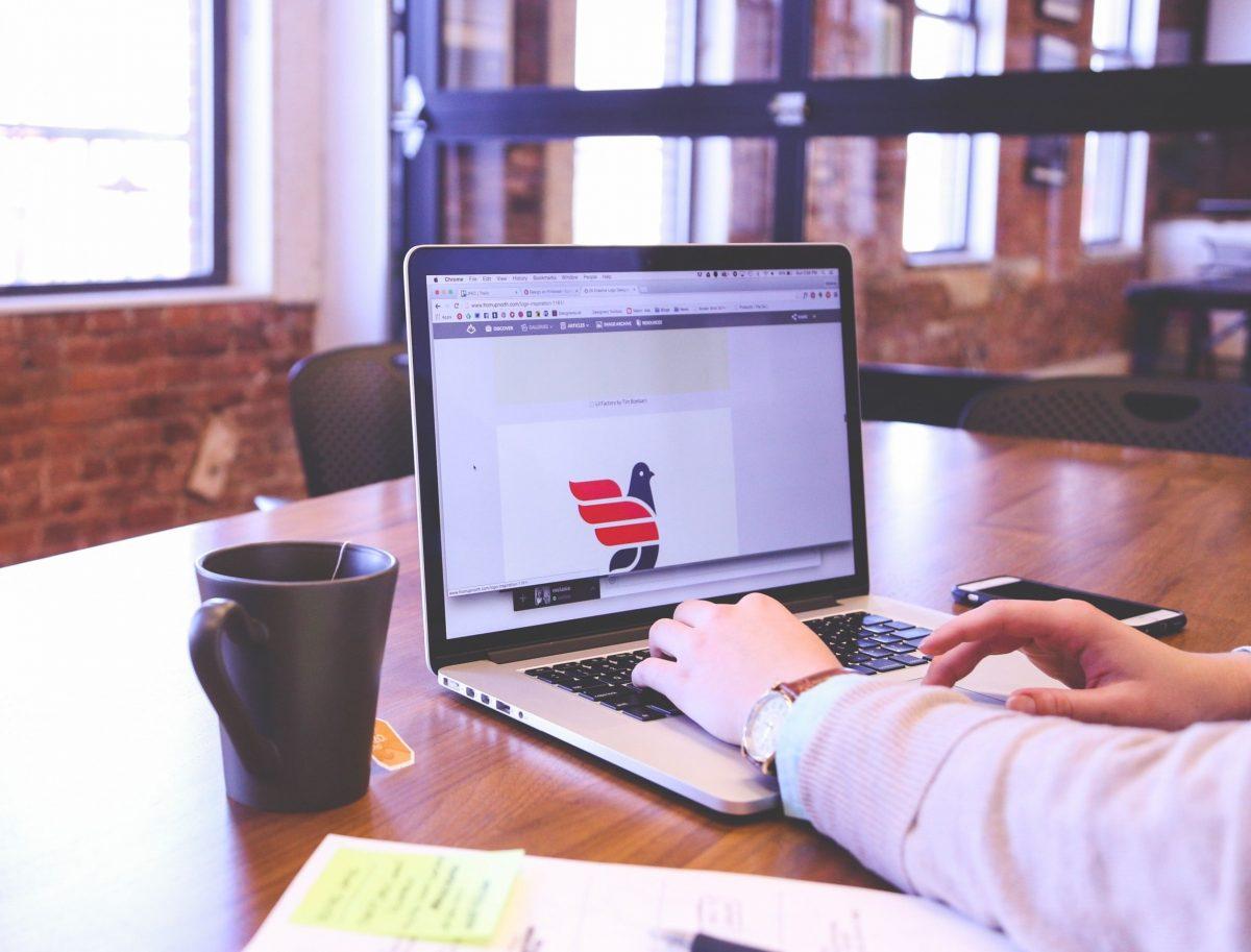 Une femme qui utilise un ordinateur portable et qui navigue sur Internet en regardant un site web.