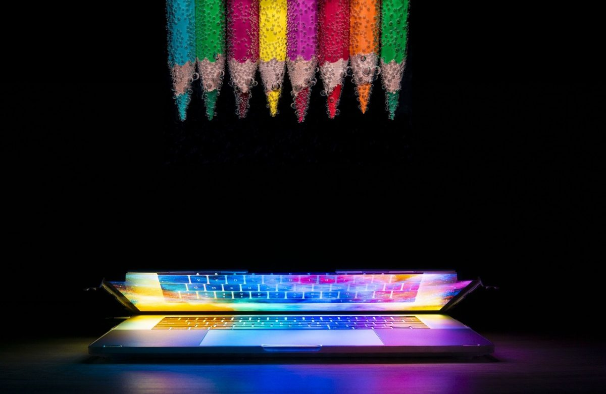 Laptop computer showing a colorful display. At the top are color pencils used for web front end design.