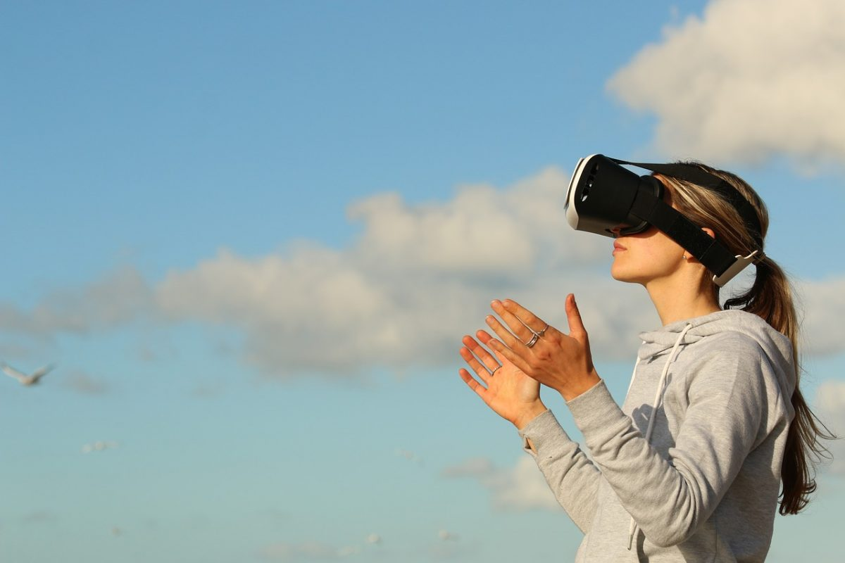 A woman using virtual reality VR googles and looking up to the sky